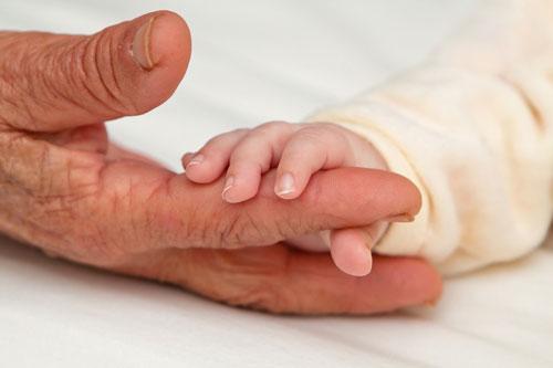 baby holding grandparent's finger
