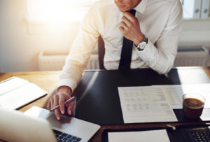 Business man working at office with laptop and documents on his desk consultant lawyer concept