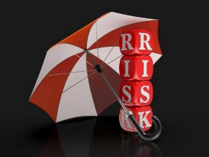 "An umbrella with wooden letter blocks underneath spelling ""risk."""