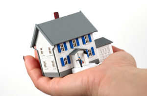 A miniature house being held in a person's hand