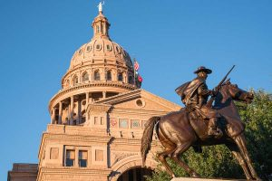 view of Texas State Capital dome seen behind the bronze statue of a Texas Ranger riding a horse