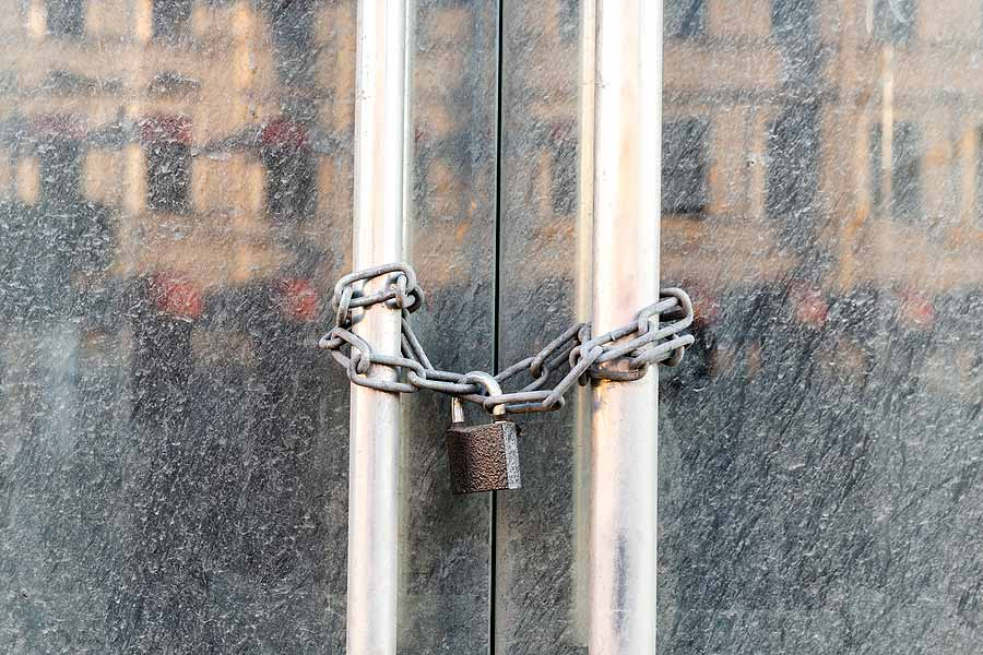 Handles on glass doors of a store locked with chain and padlock