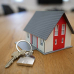 a small model of a house with a fullsize house key next to it